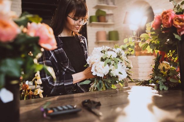 Fleuriste femme dans son propre magasin de fleurs en prenant soin de fleurs Photo gratuit