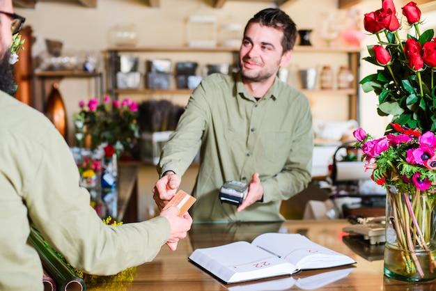 Fleuriste mâle charge un client dans un magasin de fleurs Photo Premium