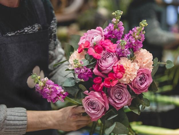 Fleuriste mâle confectionnant un bouquet de fleurs colorées Photo gratuit