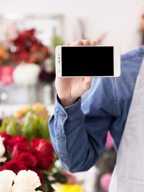 Fleuriste mâle montrant l'écran du téléphone portable dans le magasin de fleurs Photo gratuit