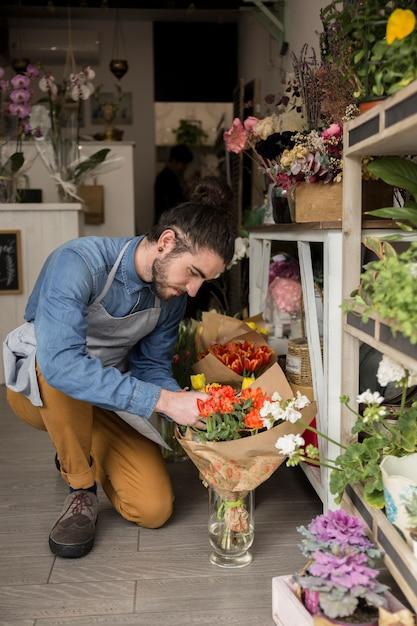 Fleuriste mâle regardant un beau bouquet de tulipes rouges dans la boutique Photo gratuit