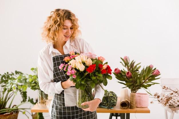 Fleuriste smiley de tir moyen tenant pot avec des fleurs Photo gratuit