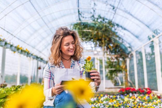 Fleuriste vérifiant l'état des fleurs en serre Photo Premium