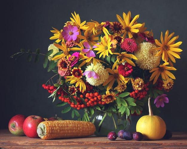Fleurs d'automne en pot, fruits et légumes sur la table Photo Premium