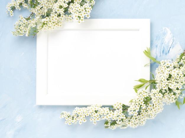 Fleurs blanches sur le cadre sur fond de béton bleu. fond de surface Photo Premium