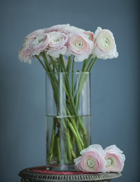 Fleurs blanches roses dans la bouteille sur la table Photo gratuit