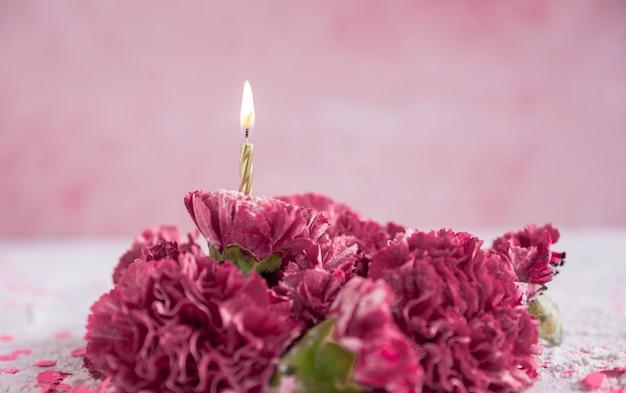 Fleurs avec bougie allumée Photo gratuit