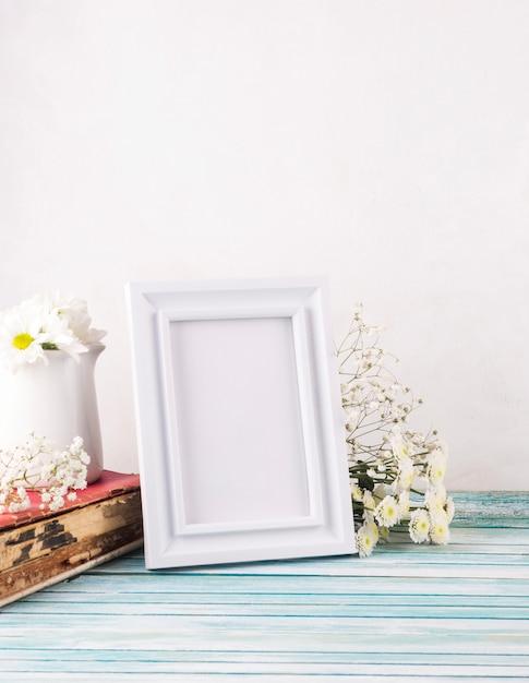 Fleurs avec cadre vierge et livre Photo gratuit