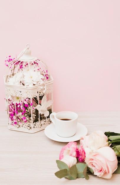 Fleurs en cage blanche; tasse à café et roses sur un bureau en bois sur fond rose Photo gratuit