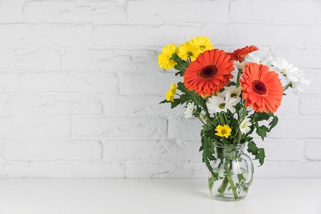 Fleurs de camomille et de gerbera dans le pichet en verre sur le bureau contre le mur de briques blanches Photo gratuit
