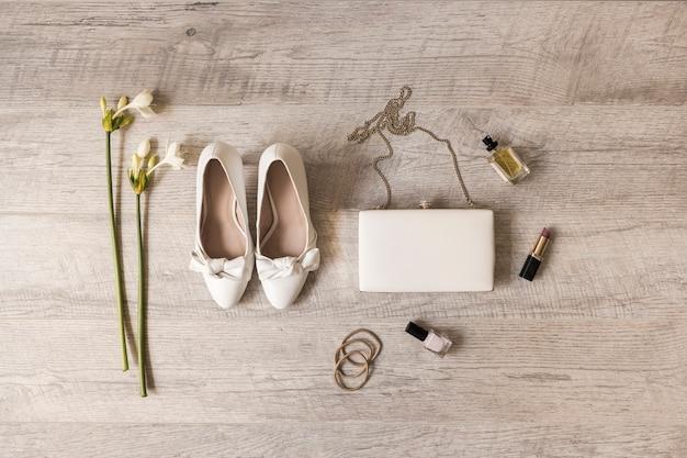 Fleurs; chaussures habillées; embrayage; parfum; rouge à lèvres; vernis à ongles et élastiques sur fond en bois Photo gratuit