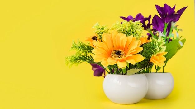 Fleurs colorées dans le petit vase blanc sur fond jaune Photo gratuit