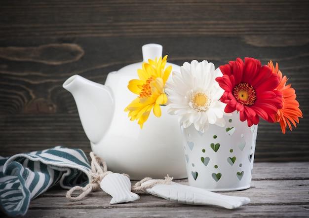 Fleurs colorées et théière sur une surface en bois sombre Photo Premium