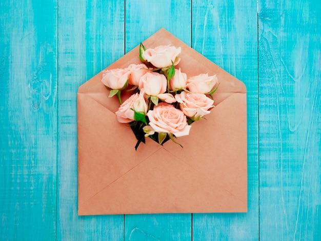 Fleurs dans une enveloppe kraft, espace copie, fond bleu Photo Premium