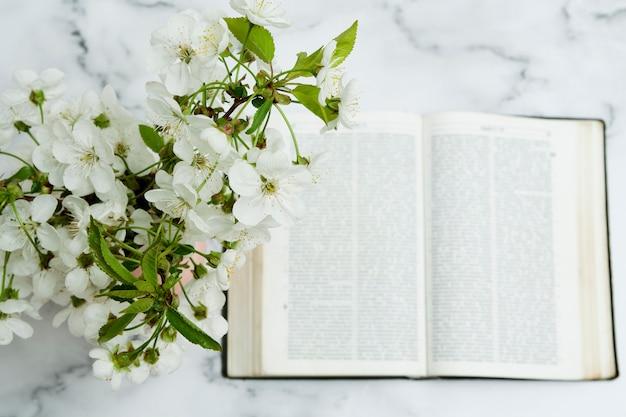 Fleurs Dans Un Vase Et Une Bible Ouverte à Plat Sur La Table Photo Premium
