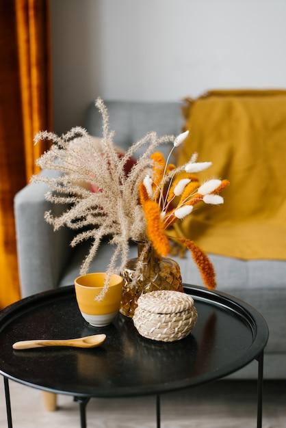 Des Fleurs Dans Un Vase Se Dressent Sur Une Table Basse Noire. Détails De L'intérieur Du Salon Dans Un Style Scandinave Minimaliste Photo Premium