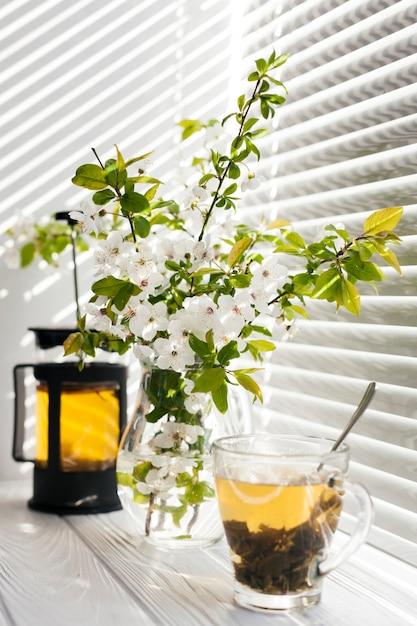 Fleurs dans un vase avec une tasse de thé Photo gratuit