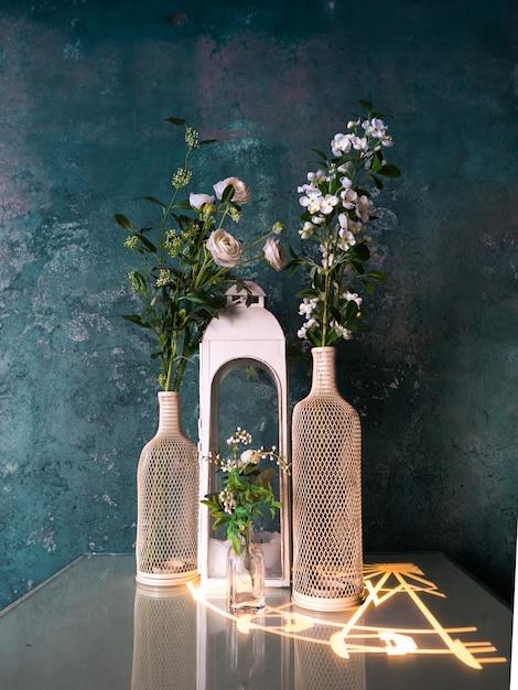Fleurs Décoratives Dans Des Vases Sur La Table Avec Mur Mur Bleu Photo Premium