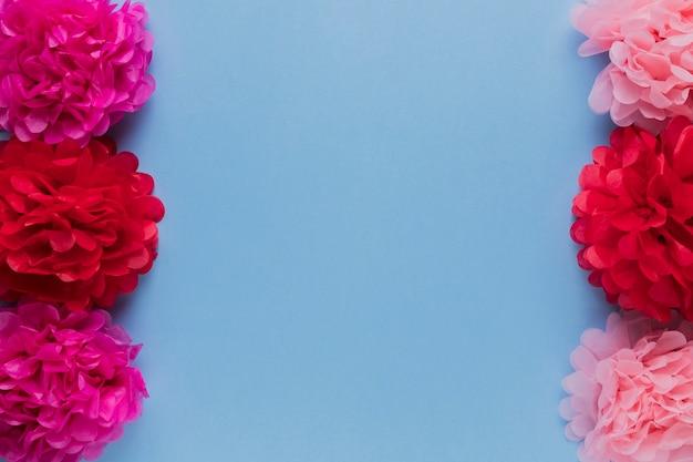 Les fleurs décoratives rouges et roses sont disposées en rangées sur la surface bleue Photo gratuit