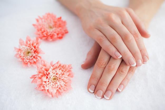 Fleurs avec des doigts manucurés français au centre de spa Photo Premium