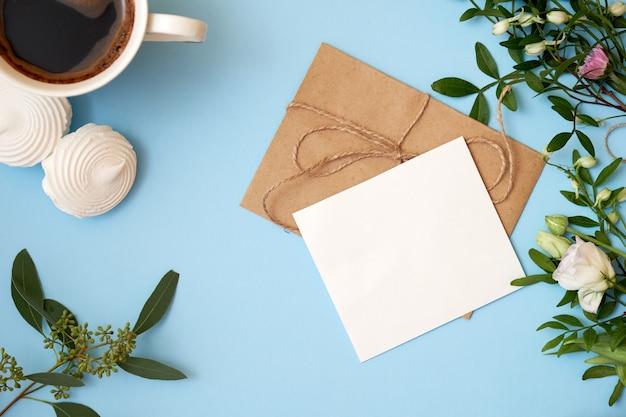 Fleurs, enveloppe d'artisanat, tasse de café sur fond bleu avec espace de copie Photo Premium