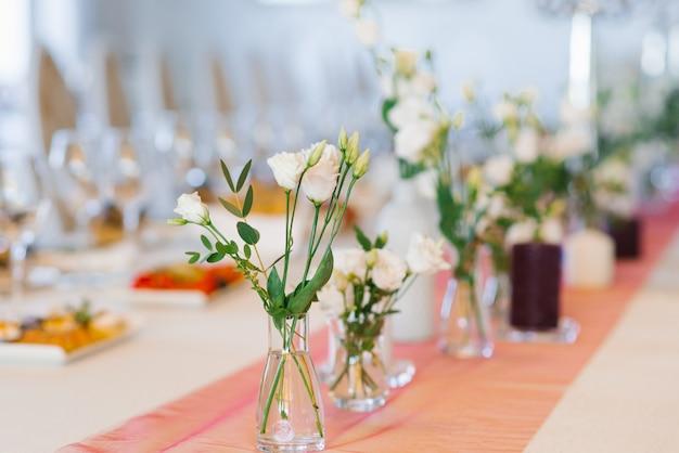 Fleurs Eustoma Blanc Se Tiennent Dans Des Vases En Verre Sur Une Table De Fête Lors D'un Mariage Photo Premium