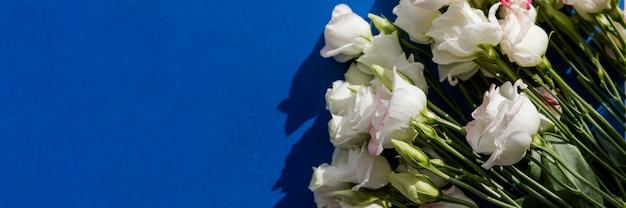 Fleurs D'eustoma Rose Blanc Sur Une Surface Bleue Dans Un Style Vintage. Vue De Dessus. Fleur De Lisianthus Blanche. Format De Bannière Pour Les Cartes D'invitation De Mariage De Félicitations. Photo Premium