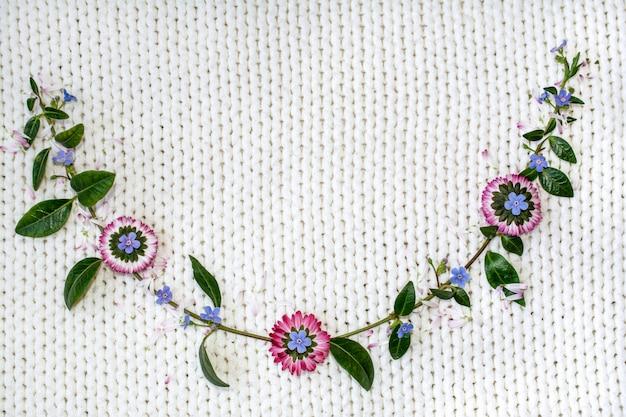 Fleurs sur un fond blanc de tricot. Photo Premium