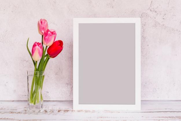 Fleurs fraîches dans un vase et un cadre Photo gratuit