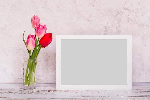 Fleurs fraîches dans un vase près du cadre Photo gratuit