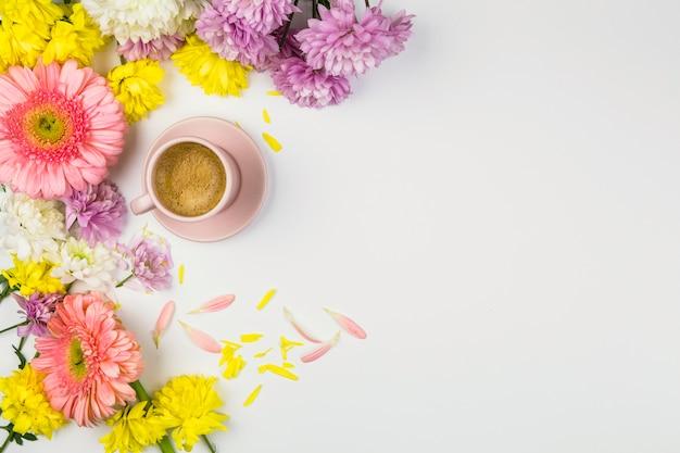 Fleurs fraîches près de tasse de boisson et de pétales Photo gratuit