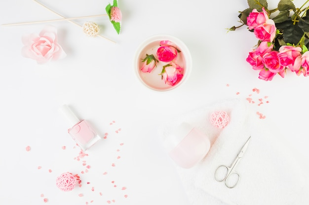 Fleurs fraîches avec des produits cosmétiques sur fond blanc Photo gratuit