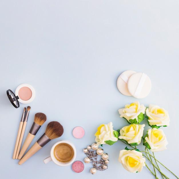 Fleurs jaunes avec produit cosmétique et tasse à café sur fond blanc Photo gratuit