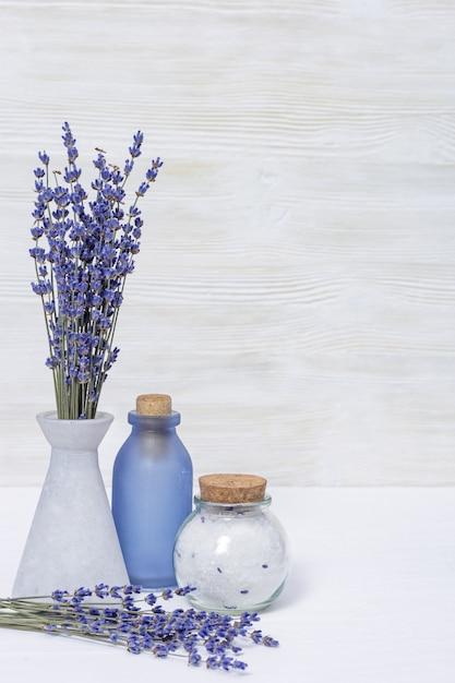 Fleurs de lavande et bouteilles en verre, sel de mer parfumé. concept de spa avec espace de copie. Photo Premium