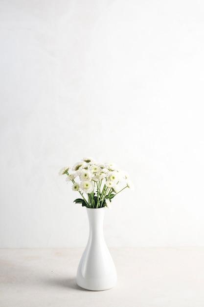 Fleurs légères dans un vase sur la table Photo gratuit