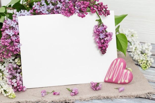 Fleurs de lilas mauve avec papier blanc sur table Photo Premium