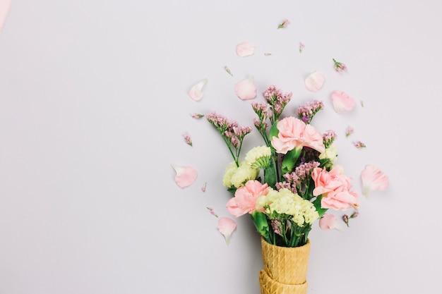 Fleurs de limonium et d'oeillets dans les cônes de gaufres isolés sur fond blanc Photo gratuit