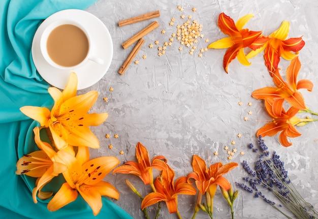 Fleurs De Lis Du Jour Et De Lavande Orange Et Une Tasse De Café Sur Un Fond De Béton Gris Avec Du Textile Bleu Photo Premium