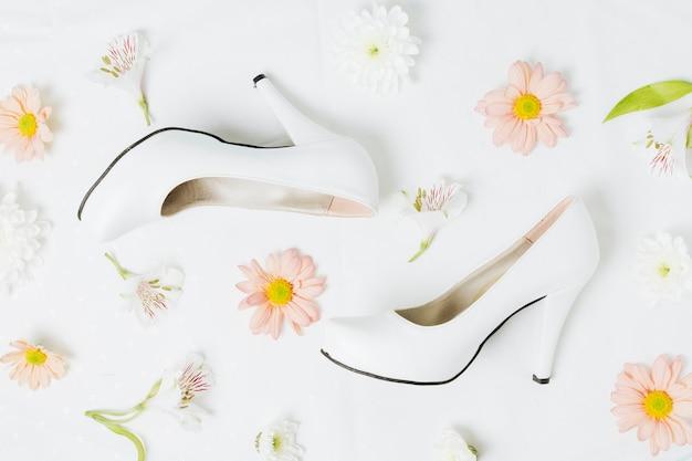 Fleurs De Lis Et De Gerbera Péruviens Avec Des Talons De Mariage Sur Fond Blanc Photo gratuit