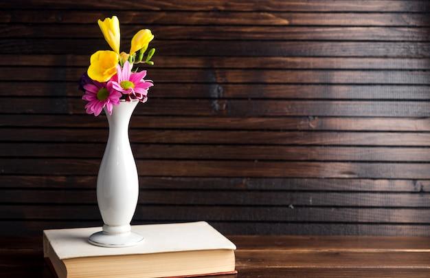 Fleurs lumineuses dans un vase sur un livre Photo gratuit