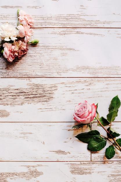Fleurs d'oeillets et rose rose sur une vieille table en bois Photo gratuit