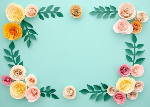 Fleurs en papier et feuilles sur fond bleu Photo gratuit