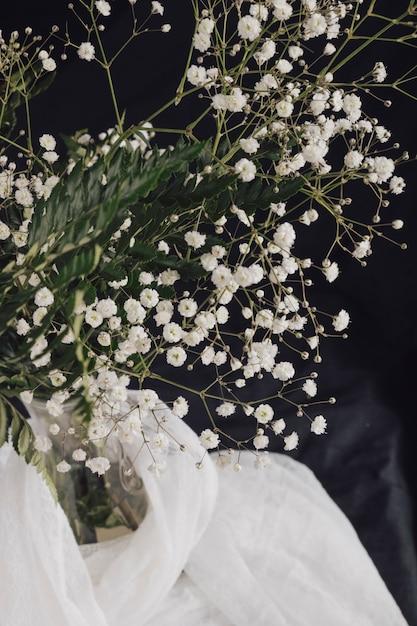 Fleurs avec des plantes dans un vase près de textile blanc Photo gratuit