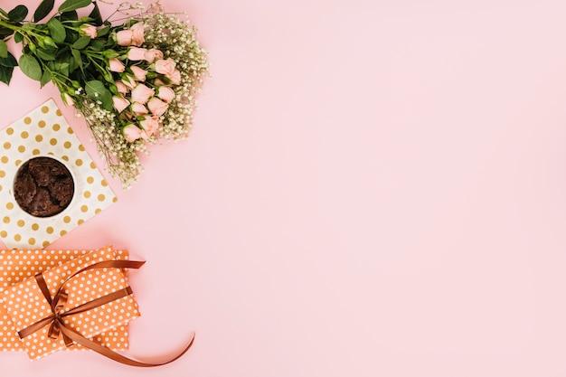Fleurs près de dessert et cadeaux Photo gratuit