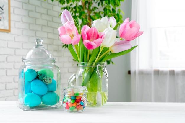 Fleurs De Printemps Fraîches Avec Des œufs Peints Pour La Célébration De Pâques Photo Premium