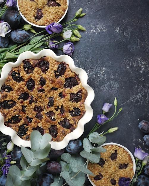 Fleurs de printemps, prunes et tarte à la crème dans un bol Photo Premium