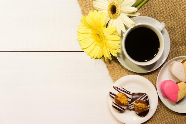 Fleurs romantiques avec café et friandises sur la table Photo Premium
