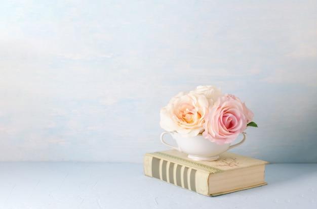 Fleurs De Rose Artificielles Dans Une Tasse Blanche Avec Un Vieux Livre Sur Bleu Photo Premium
