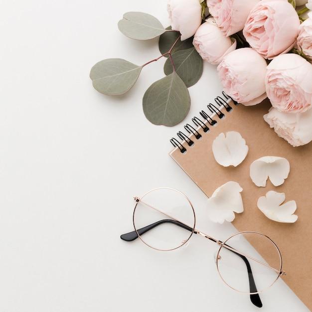 Fleurs Roses Avec Arrangement De Feuilles Avec Des Lunettes Haute Vue Photo gratuit