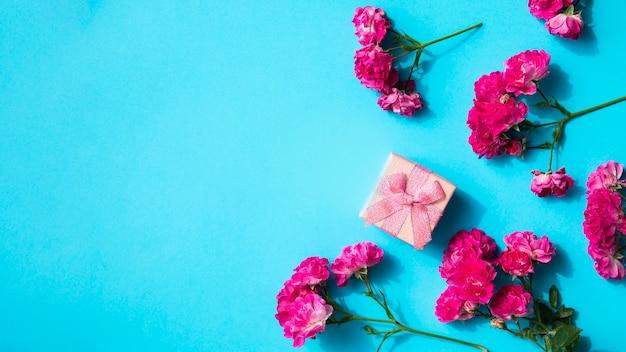 Fleurs roses et cadeau sur fond bleu Photo gratuit
